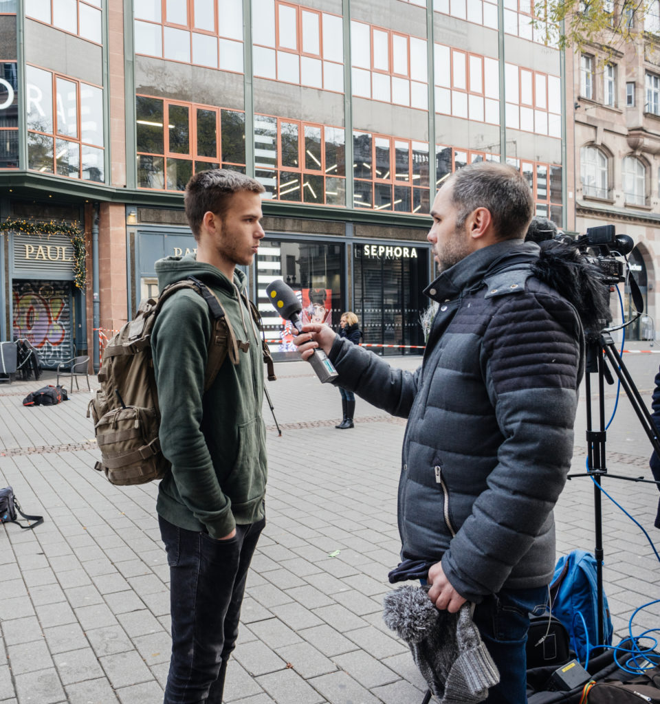 STRASBOURG, FRANCE - DEC 11, 2018: Journalist talking with French young man after the terrorist attack in the Strasbourg Christmas market area